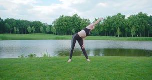 Frontowy widok dosyć elastyczna kobieta robi pilates i joga na łące blisko rzeki zbiory