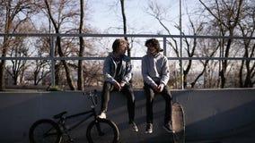 Frontowy widok dwa przyjaciół deskorolkarz i bmx jeździec siedzimy wpólnie na wysokim parapet w miasto łyżwy parku zbiory