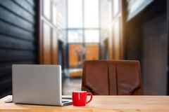 Frontowy widok filiżanka, komputer, smartphone i pastylka na stole w biurze, zdjęcie royalty free
