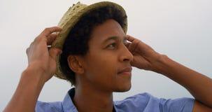 Frontowy widok jest ubranym kapelusz na plaży 4k amerykanin afrykańskiego pochodzenia mężczyzna zdjęcie wideo