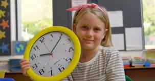 Frontowy widok Kaukaska uczennica z ściennego zegaru obsiadaniem przy biurkiem w sali lekcyjnej 4k zbiory