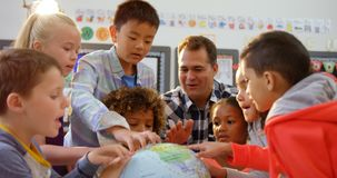 Frontowy widok Kaukaski m?ski nauczyciel uczy dzieciak?w o kuli ziemskiej w sali lekcyjnej 4k zdjęcie wideo