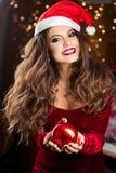 Frontowy widok kobieta utrzymuje boże narodzenia w czerwonym Santa kapeluszu bawi się obraz royalty free