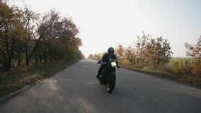 Frontowy widok mężczyzna w czarnym hełma i skórzanej kurtki jeździeckim motocyklu na wiejskiej drodze zdjęcie wideo