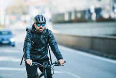Frontowy widok męski rowerowy kurier dostarcza pakunki w mieście kosmos kopii zdjęcia royalty free