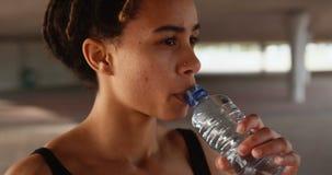 Frontowy widok młoda amerykanin afrykańskiego pochodzenia kobiety woda pitna w mieście 4k zbiory wideo