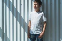 Frontowy widok Młoda modniś chłopiec ubierająca w białej koszulce jest stojakami salowymi przeciw biel ścianie Egzamin próbny Up  Obrazy Royalty Free