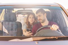 Frontowy widok nieogolony męski kierowca siedzi przy kołem i jedzie jego samochód trzyma mądrze telefon i podczas gdy jego żona s obraz royalty free