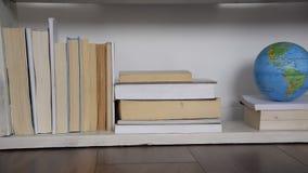 Frontowy widok półka z książkami i kulą ziemską zbiory wideo
