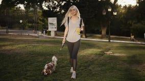 Frontowy widok piękna smilling kobieta z długim blondynka włosy odprowadzeniem z jej psem w parku Jest być ubranym przypadkowy zdjęcie wideo