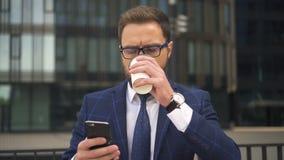 Frontowy widok pije kawę biznesmen, patrzeje smartphone ekran na ulicie zbiory wideo