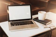 Frontowy widok pusty miejsce pracy Na białym stolik do kawy jest laptop z pustym ekranem, filiżanka kawy, notatnik, pióro, gazeta Fotografia Royalty Free