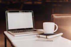 Frontowy widok pusty miejsce pracy Na białym stolik do kawy jest laptop z pustym ekranem, filiżanka kawy, notatnik, pióro, gazeta fotografia stock