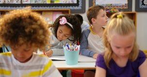 Frontowy widok ras schoolkids rysuje na notatniku w sali lekcyjnej 4k zbiory wideo