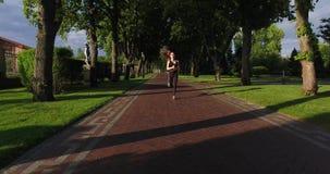 Frontowy widok sportowa kobieta jogging wzdłuż drogi zdjęcie wideo
