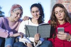 Frontowy widok trzy dziewczyny siedzi na ziemi outdoors Jeden one używa telefon komórkowego podczas gdy odpoczynek patrzeje książ zdjęcia stock