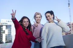 Frontowy widok trzy nastoletniej dziewczyny robi pokoju znakowi outdoors w słonecznym dniu zdjęcia stock