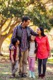 Frontowy widok uśmiechnięta rodzinna pozycja przy parkiem Fotografia Royalty Free