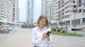 Frontowy widok zdumiony kobiety odprowadzenie sprawdza mądrze telefon zawartość zbiory wideo