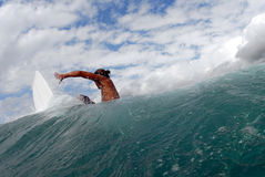 Frontside off the lip. A surfer doing a frontside turn in hawaii. a view from the back of the wave Stock Image