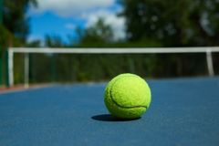 Frontview of bright tennis ball on blue carpet of opened court. royalty free stock image