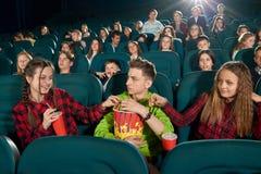 Frontview de trois amis mangeant du maïs éclaté en observant le film Photo stock