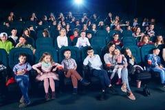 Frontview della gente che si siede nel corridoio del cinema Fotografia Stock