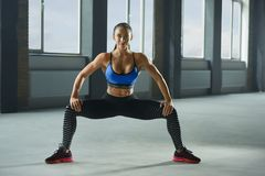 Frontview der attraktiven Frau mit dem athletischen Körper, der sitzen oben und Abstiege tut lizenzfreies stockbild