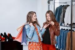 Frontview des filles achetant des vêtements pendant les achats au mail Image stock