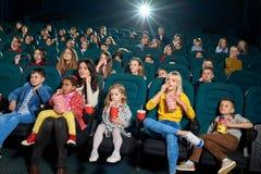 Frontview emocjonalni dorosli i dzieci ogląda film w nowym kinie fotografia royalty free