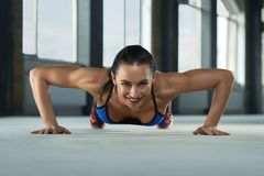 Frontview of young sporty girl with athletic body doing push ups on gym floor. royalty free stock image