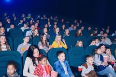 Frontview of young people watching movie in cinema. Frontview of young exited people watching interesting movie in cinema hall. Boys and girls look very Stock Photography