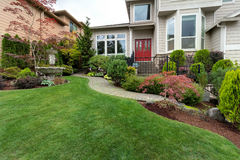 Frontyard of House with Water Fountain. Frontyard garden of house with water fountain green grass lawn paver brick path trees and shrubs landscaping Stock Photography