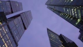 Froschperspektive der Kamera drehend vor futuristischen Wolkenkratzern abend stock video footage