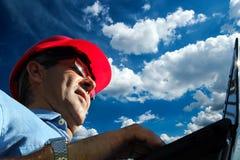 Froschperspektive einer Ingenieur-At Work With-Laptop-Computers gegen blauen Himmel während Sunny Days lizenzfreie stockfotos