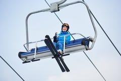 Froschperspektive eines lächelnden weiblichen Skifahrers im blauen Skianzug, der bis zur Spitze des Berges auf einen Kabelskiaufz Stockfotos