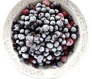 Frosen cranberries and black currant berries in white bowl isola Royalty Free Stock Photography