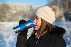 Frost concept - beautiful woman with thermal mug in winter fores Royalty Free Stock Photos