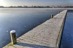Footbridge across a frozen lake. Frost-covered wooden walkbridge across frozen lake Kralingse Plas in Rotterdam, The Netherlands with the city`s skyline in the royalty free stock photo