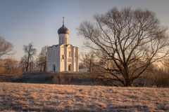 The frost on the grass blazes in the rays of the cold, blooming sun, beautifully outlining the silhouettes of trees and an ancient. View to the Church of the Stock Photos