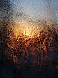 Frost ice crystals and water drops on window glass on the background of sunrise. Frost ice crystals and water drops on window glass on the background of rising Stock Image
