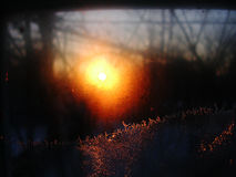 Frost ice crystals and water drops on window glass on the background of sunrise. Stock Photo