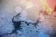Frost on window. Glare through glass. Festive background with winter theme. bokeh blurred abstract colorful background. Frost and ice on the window. Glare stock photos