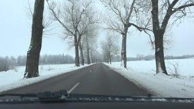 Автомобиль на пустом переулке дороги в зиме Frost и снег покрыли деревья 4K видеоматериал