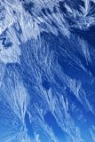 Frost pattern on a window glass. Textures and backgrounds: ice crystals on the window, frost texture over the blue sky gradient. Abstract winter pattern Royalty Free Stock Image