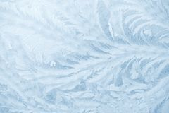 Frost patterns on window glass in winter season. Frosted Glass Texture. Blue background. Frost patterns on window glass in winter season. Frosted Glass Texture stock image