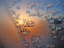 Frost and sun. Frosty natural pattern with sun on winter window Royalty Free Stock Image