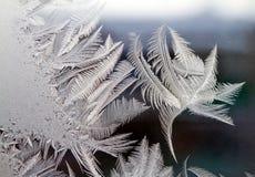 Frost zeichnet Eishintergrundmuster auf einer Fensterscheibe Stockfotografie