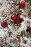 Frostad vit julgran med röda prydnader Fotografering för Bildbyråer