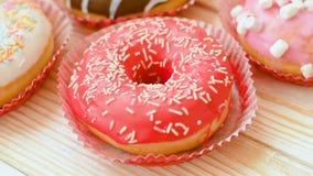 Frostade donuts med färgrika stänk stock video